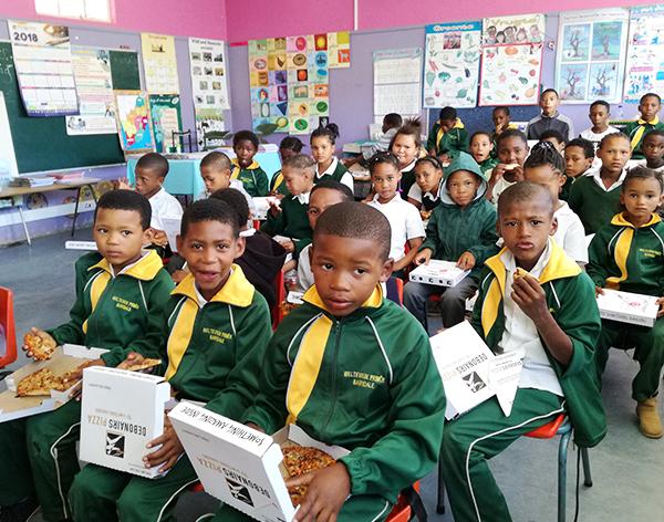 School kids in classroom eating pizza