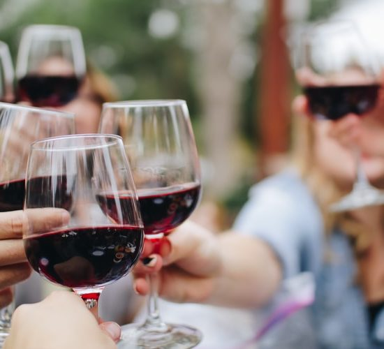 People cheersing with red wine